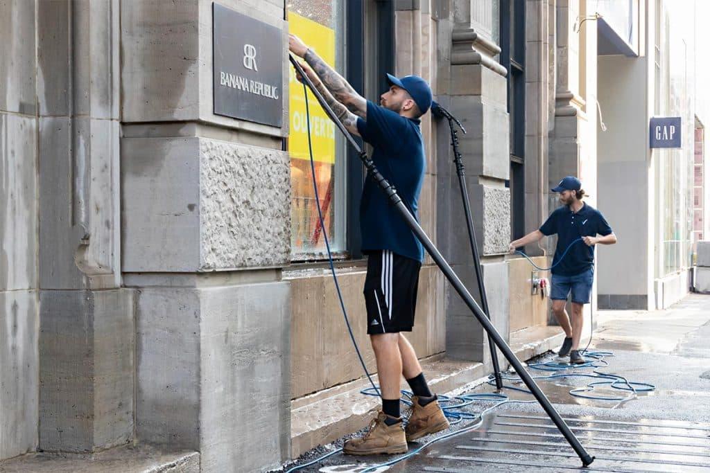 Deux techniciens de Vitres.net lavent les fenêtres du Banana Republic au Centre-Ville de Montréal