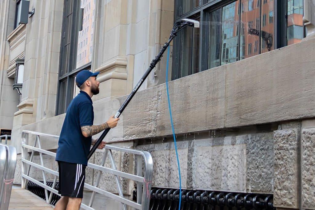 Le chef d'équipe de Vitres.net rince à l'eau pure les fenêtres d'un immeuble commercial