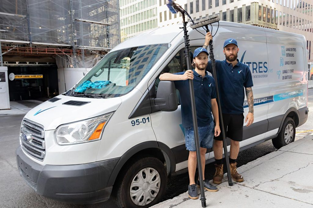 Deux techniciens de Vitres.net tiennent leur brosse à eau pure devant le camion-usine